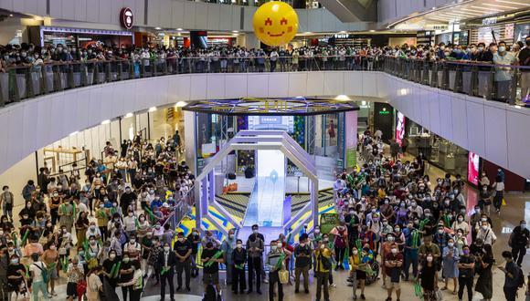 La gente en un centro comercial viene a ver a Siobhan Haughey en Hong Kong el 30 de julio de 2021, mientras gana una medalla de plata en los 100 metros libres femeninos en los Juegos Olímpicos de Tokio. (Foto de ISAAC LAWRENCE / AFP)