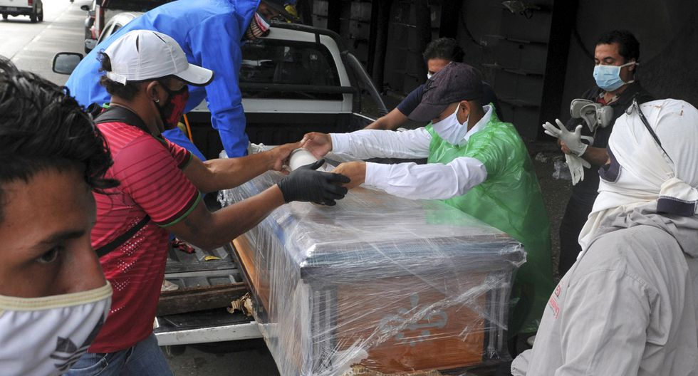Imagen referencial. Personas son vistas en los exteriores de un cementerio en Guayaquil, Ecuador. (AFP/José Sánchez Lindao).