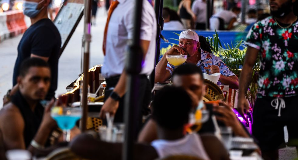 Un hombre disfruta de una bebida en un restaurante en Ocean Drive en Miami Beach, Florida (Estados Unidos), el 14 de julio de 2020, en medio de la pandemia de coronavirus. (AFP / CHANDAN KHANNA).
