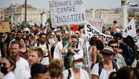 """Un manifestante sostiene un cartel que dice """"Trabajadores de la salud unidos contra la injusticia"""" durante una manifestación contra la vacunación obligatoria para ciertos trabajadores y el uso obligatorio del pase de salud convocado por el gobierno francés, en Marsella. (CLEMENT MAHOUDEAU / AFP)"""