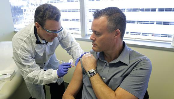 EN EE.UU. El farmacéutico Michael Witte (izquierda) aplica la vacuna contra el COVID-19 de la empresa Moderna a Neal Browning (derecha), que forma parte del primer grupo de voluntarios.