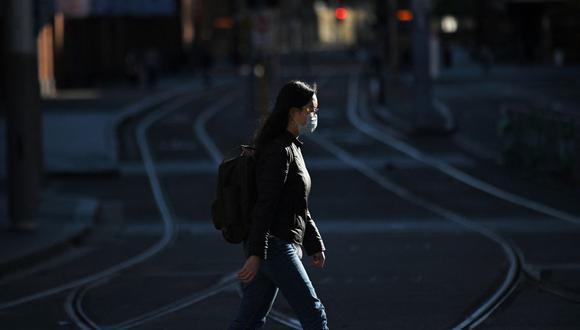 Una mujer con una máscara cruza las vías del tranvía en el distrito comercial central vacío en Sídney (Australia), el 27 de junio de 2021. (STEVEN SAPHORE / AFP).