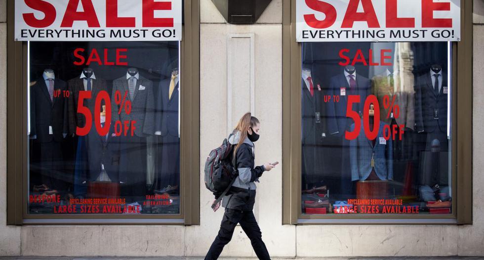 Imagen referencial. Una mujer que usa una cubierta protectora para combatir la propagación del coronavirus pasa junto a los carteles de ventas en los escaparates de una tienda en Londres, el 10 de noviembre de 2020. (Tolga Akmen / AFP).
