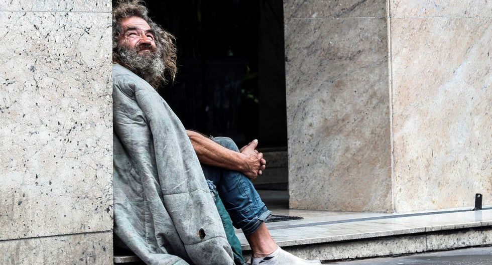 """Un """"sin casa"""" descansa el jueves 13 de febrero en la acera de la avenida Paulista, en la ciudad de Sao Paulo (Brasil). (EFE)."""