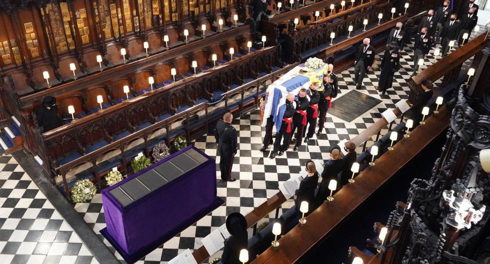 La reina Isabel II (izq.) observa cómo llevan el ataúd del príncipe Felipe de Gran Bretaña, duque de Edimburgo, durante su funeral dentro de la Capilla de San Jorge en el Castillo de Windsor en Windsor, al oeste de Londres, el 17 de abril de 2021. (Dominic Lipinski / POOL / AFP).