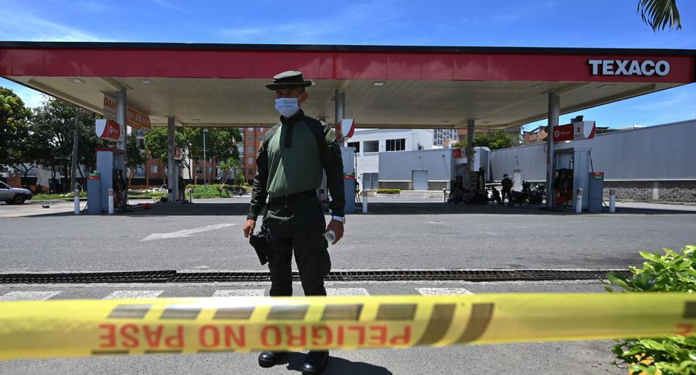 Un policía hace guardia en una gasolinera para evitar una posible destrucción en el marco de las protestas contra el gobierno del presidente Iván Duque, en Cali, Colombia, el 7 de mayo de 2021. (Luis ROBAYO / AFP).