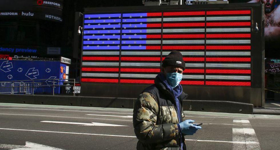 Un hombre usa una máscara facial mientras camina por un Times Square desierto por la pandemia de coronavirus en Nueva York, Estados Unidos. (Foto: AFP)