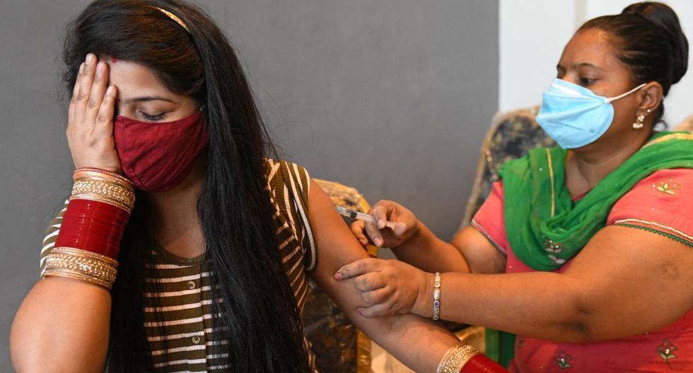Una trabajadora de la salud vacuna a una mujer con la vacuna Covishield contra el coronavirus Covid-19 en Amritsar, India, el 20 de junio de 2021. (Foto de Narinder NANU / AFP).