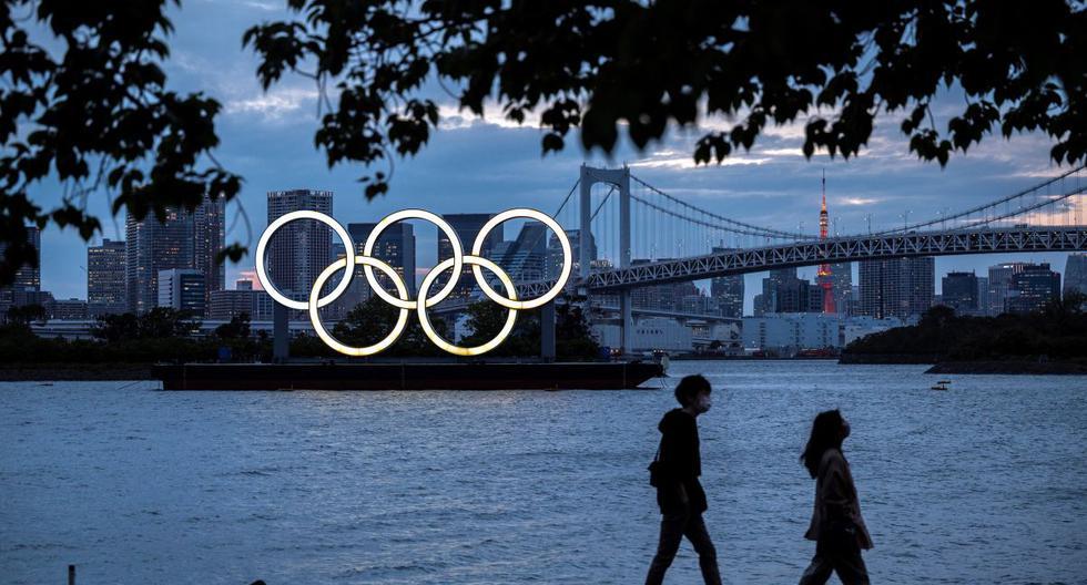 Esta fotografía de archivo tomada el 28 de abril de 2021 muestra una vista general de los anillos olímpicos iluminados al anochecer en el paseo marítimo de Odaiba en Tokio. (CHARLY TRIBALLEAU / AFP).