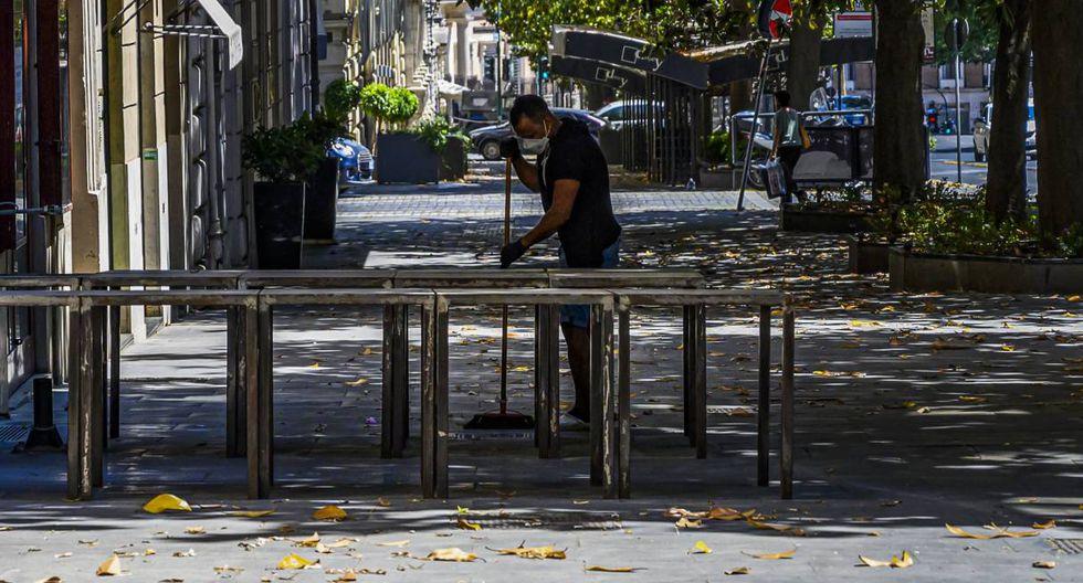 Un hombre barre el pavimento fuera de las tiendas en Via Veneto, en el centro de Roma. (Tiziana FABI / AFP).