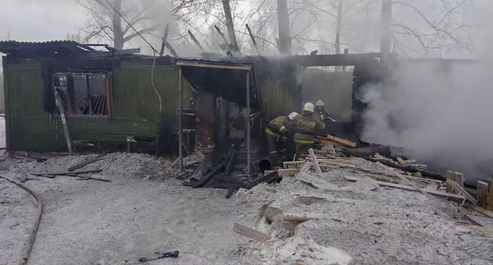 Esta fotografía del Ministerio de Emergencias de Rusia muestra a los bomberos que trabajan en el lugar del incendio que se produjo en una choza de madera. (AFP)